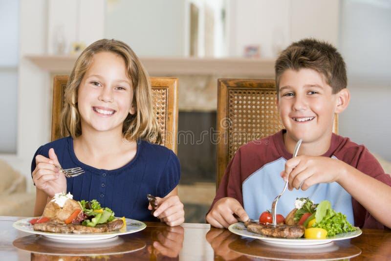 Hermano y hermana que comen la comida, mealtime junto fotografía de archivo