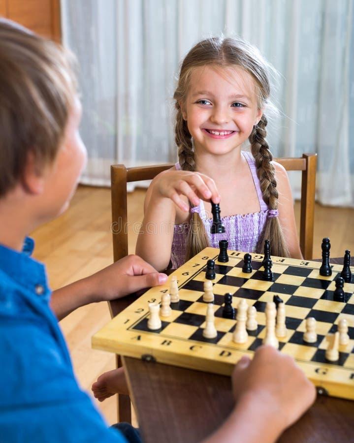 Hermano y hermana que juegan a ajedrez imagen de archivo