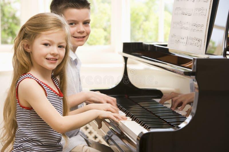 Hermano y hermana que juegan el piano imagen de archivo