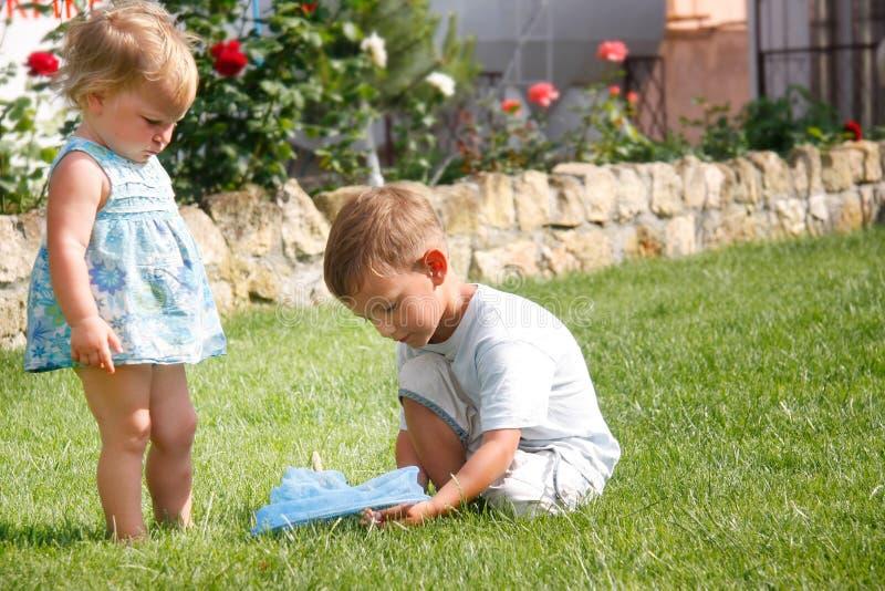 Hermano y hermana que juegan en parque foto de archivo libre de regalías