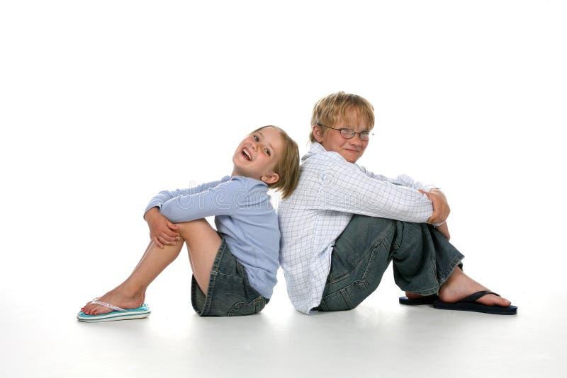 Hermano y hermana que se sientan junto fotografía de archivo