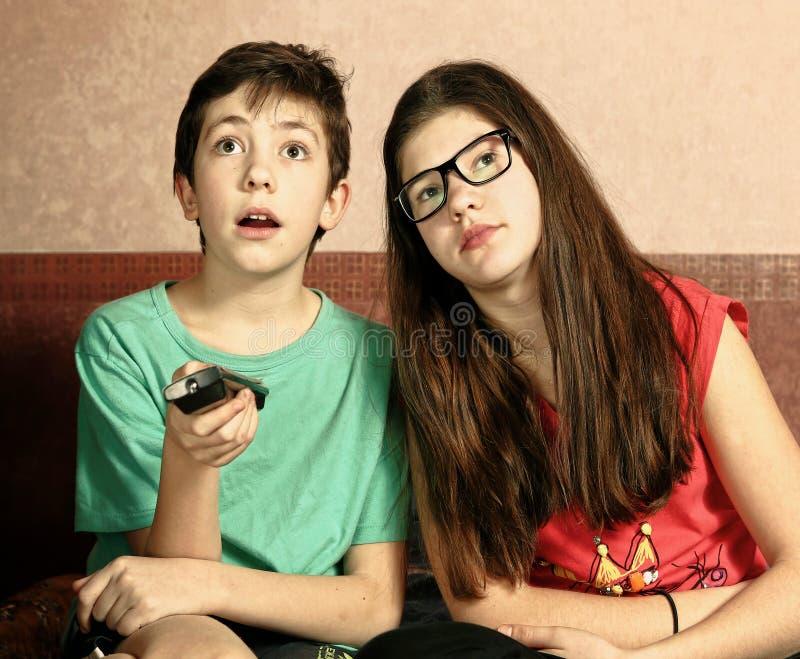 Hermanos adolescentes hermano y hermana que ven la TV foto de archivo libre de regalías