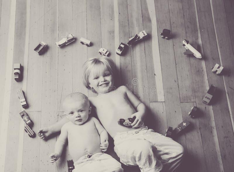 Hermanos cercados por un corazón hecho de los trenes y de los vehículos de madera fotos de archivo
