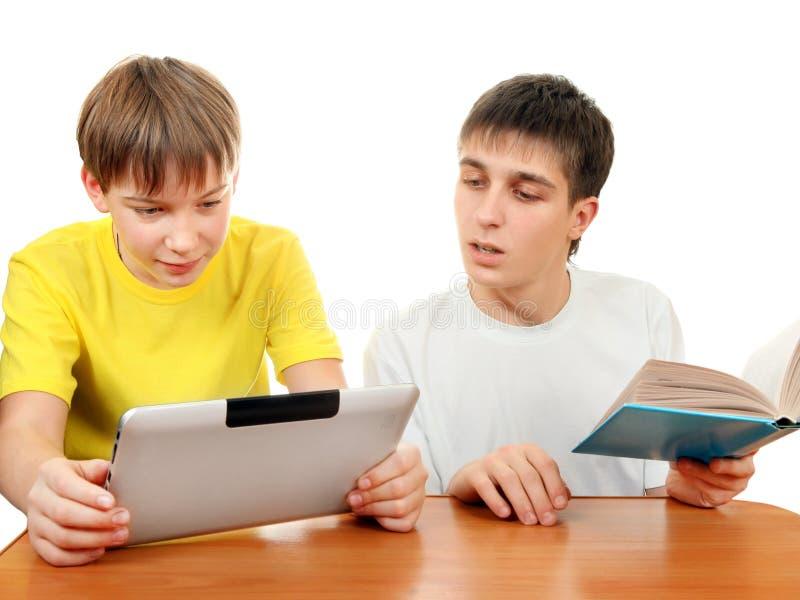 Hermanos con un libro y una tableta imagen de archivo libre de regalías