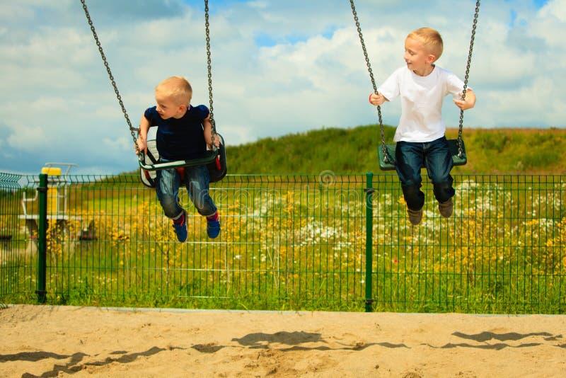 Hermanos de los niños pequeños que se divierten en un oscilación al aire libre imagen de archivo