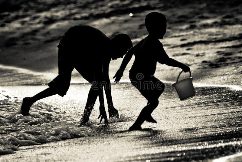Hermanos de los hermanos que juegan la cogida en una playa en Singapur fotografía de archivo libre de regalías