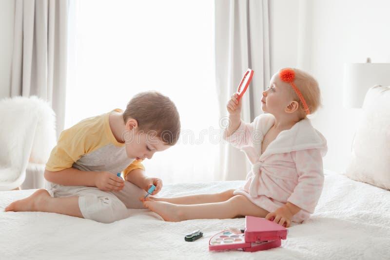 Hermanos del muchacho y de la muchacha que juegan junto los clavos de pintura que se sientan en cama en casa imagenes de archivo