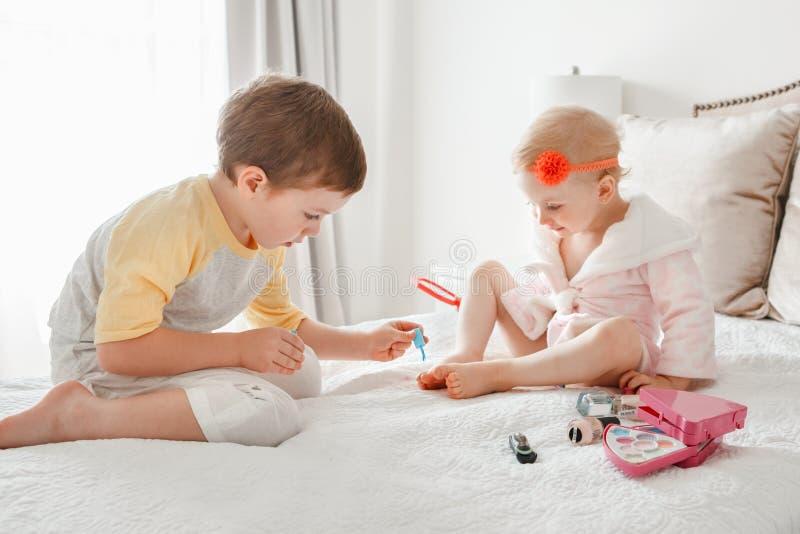 Hermanos del muchacho y de la muchacha que juegan junto los clavos de pintura que se sientan en cama en casa imagen de archivo