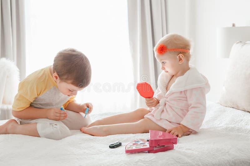 Hermanos del muchacho y de la muchacha que juegan junto los clavos de pintura que se sientan en cama en casa fotos de archivo libres de regalías