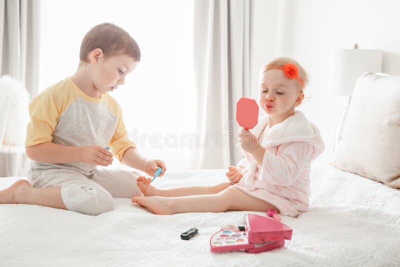 Hermanos del muchacho y de la muchacha que juegan junto los clavos de pintura que se sientan en cama en casa fotografía de archivo libre de regalías
