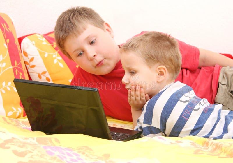Hermanos en la computadora portátil imagen de archivo