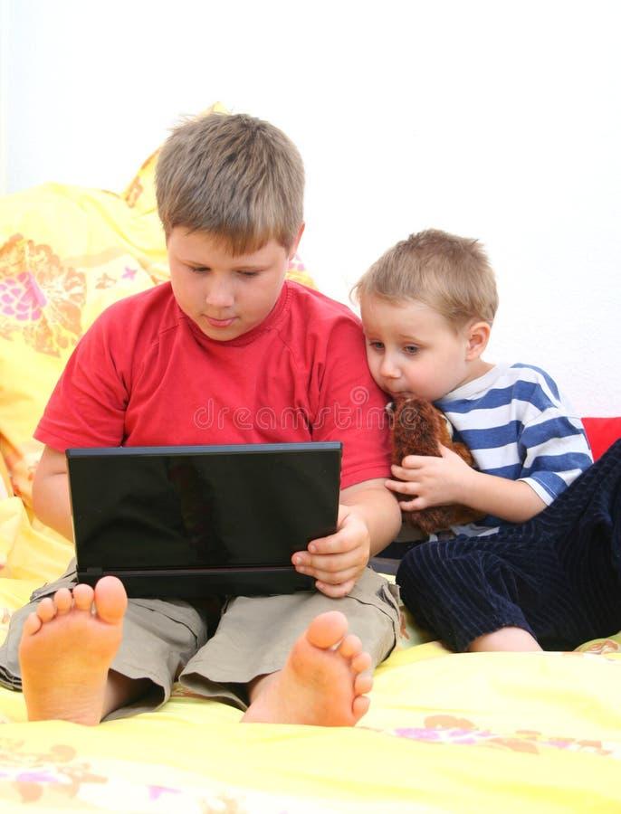 Hermanos en la computadora portátil foto de archivo libre de regalías
