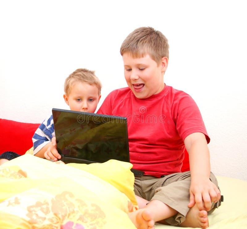Hermanos en la computadora portátil fotos de archivo