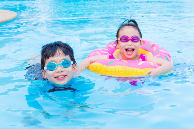 Hermanos felices junto en piscina imágenes de archivo libres de regalías