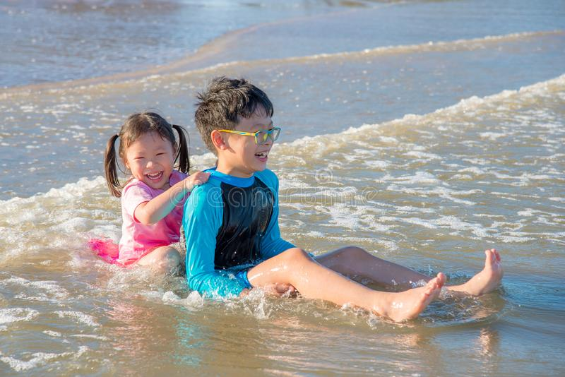 Hermanos felices que juegan en la playa foto de archivo