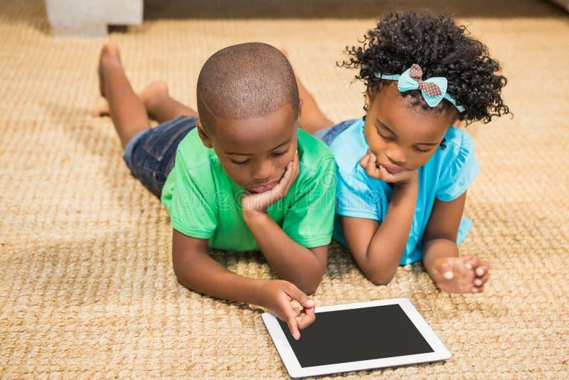 Hermanos felices que mienten en el piso usando la tableta foto de archivo libre de regalías