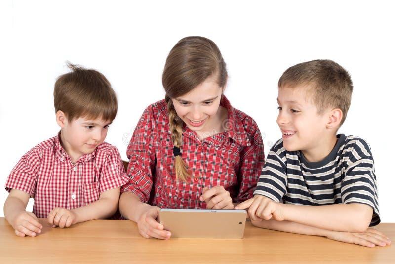 Hermanos felices que se sientan en el escritorio y que usan la tableta aislada en blanco foto de archivo libre de regalías