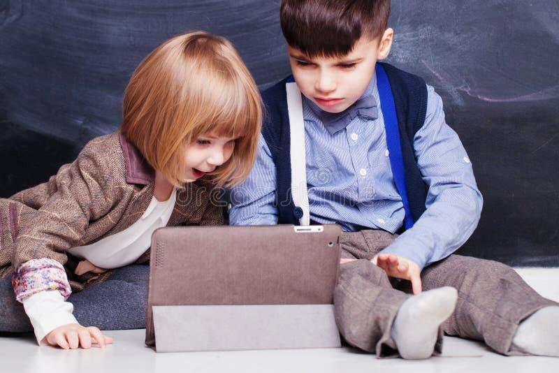 Hermanos felices que usan la tableta de la PC y jugando junto Cabritos en el país imagen de archivo
