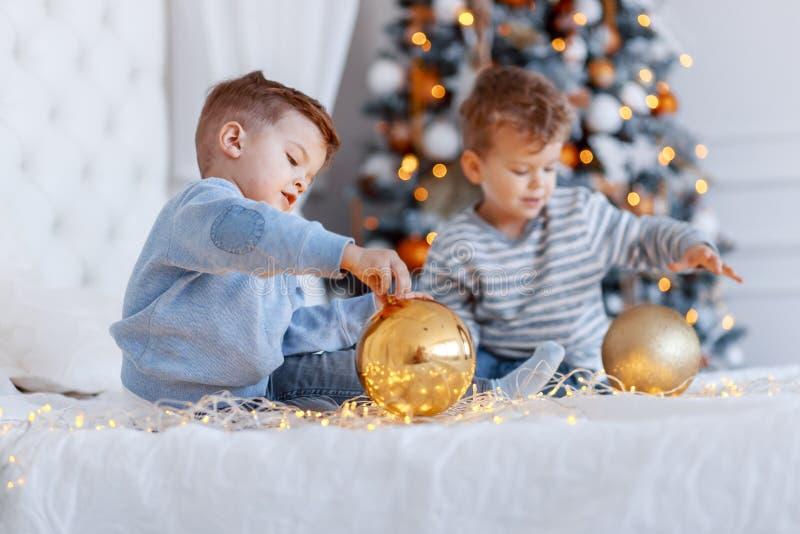Hermanos gemelos delante del árbol de navidad con las velas y los regalos amor, felicidad y concepto de familia grande fotos de archivo