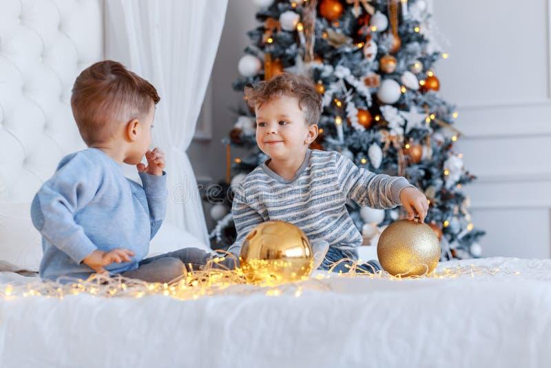 Hermanos gemelos delante del árbol de navidad con las velas y los regalos amor, felicidad y concepto de familia grande fotografía de archivo libre de regalías