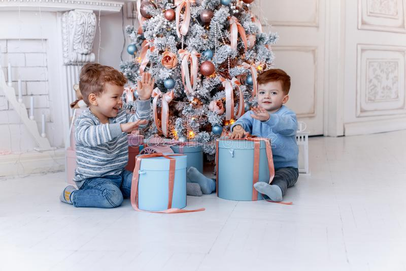 Hermanos gemelos delante del árbol de navidad con las velas y los regalos amor, felicidad y concepto de familia grande foto de archivo libre de regalías