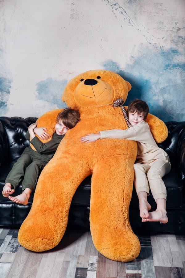 Hermanos gemelos felices en los pijamas que abrazan la sonrisa feliz de peluche del juguete suave grande del oso en casa fotografía de archivo libre de regalías