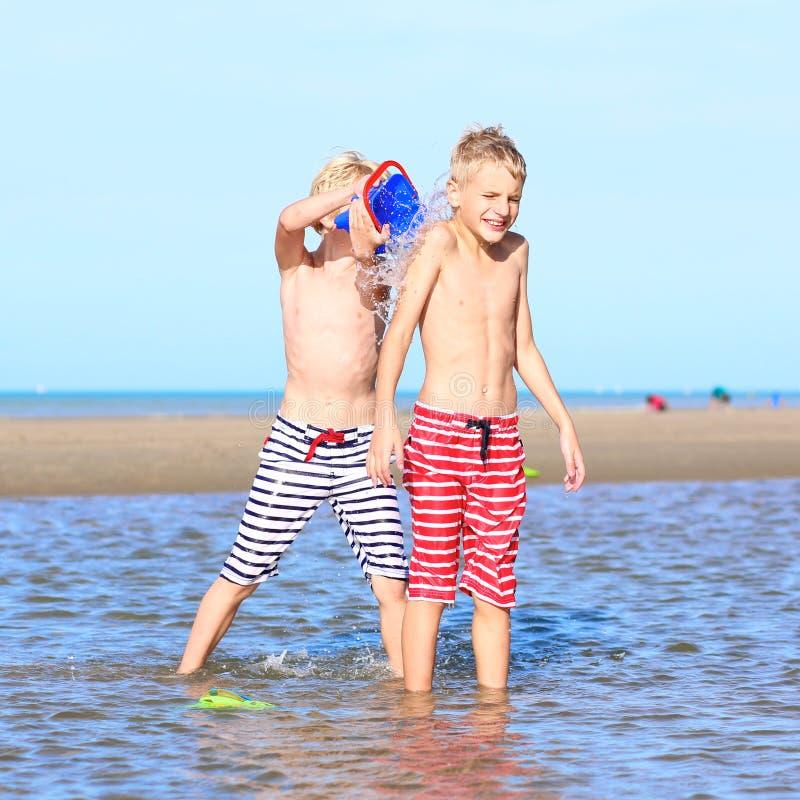 Hermanos gemelos que juegan en la playa fotos de archivo
