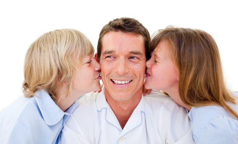 Hermanos lindos que besan a su padre foto de archivo