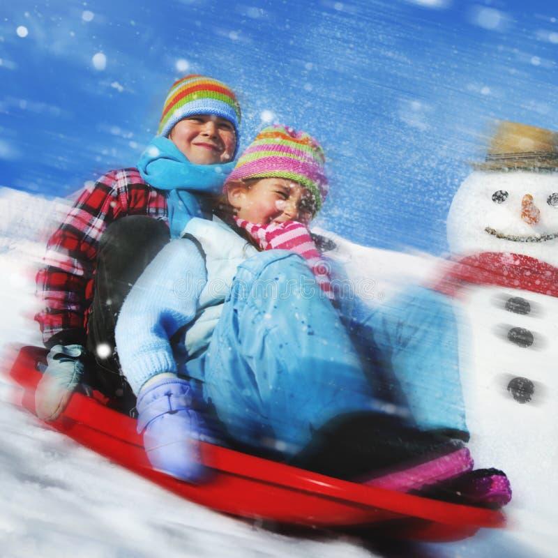 Hermanos que juegan el trineo de la nieve en el concepto de la nieve fotos de archivo