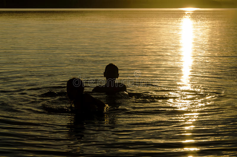 Hermanos que juegan en el agua de un lago en la puesta del sol fotos de archivo