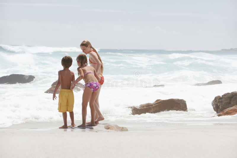 Hermanos que juegan en la playa fotos de archivo