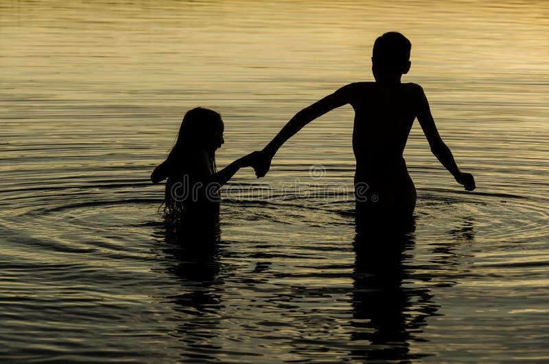 Hermanos que llevan a cabo las manos en el agua de un lago en la puesta del sol imágenes de archivo libres de regalías