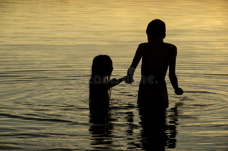 Hermanos que llevan a cabo las manos en el agua de un lago en la puesta del sol foto de archivo