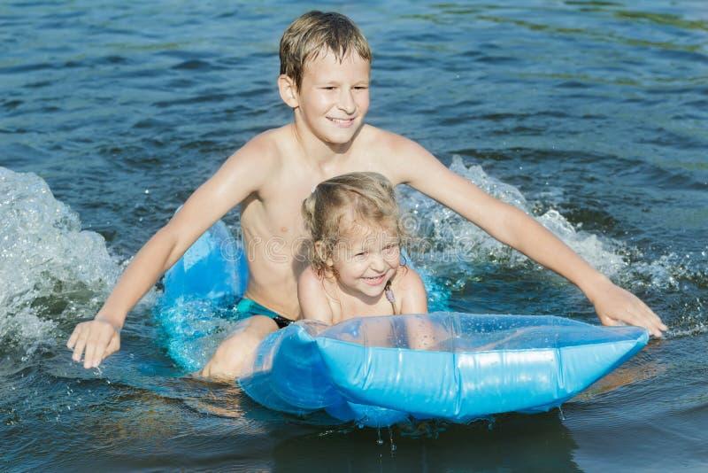 Hermanos que se divierten durante el baño de mar del verano con la estera azul del aire de la piscina del huevo del petirrojo al  imágenes de archivo libres de regalías
