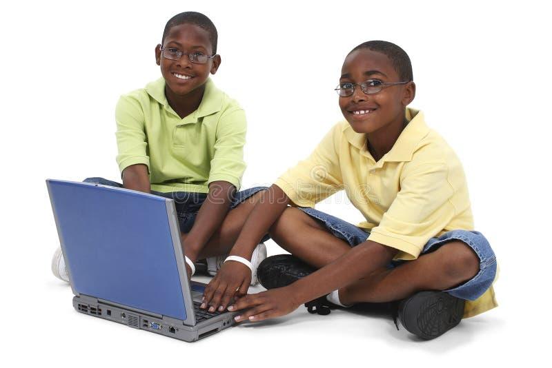 Hermanos que trabajan en el ordenador portátil que se sienta en suelo