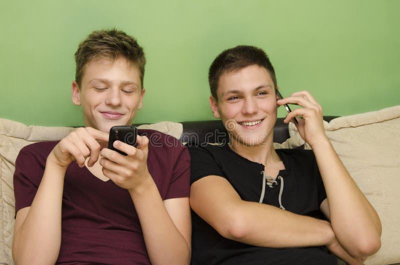 Hermanos que usan los teléfonos elegantes foto de archivo