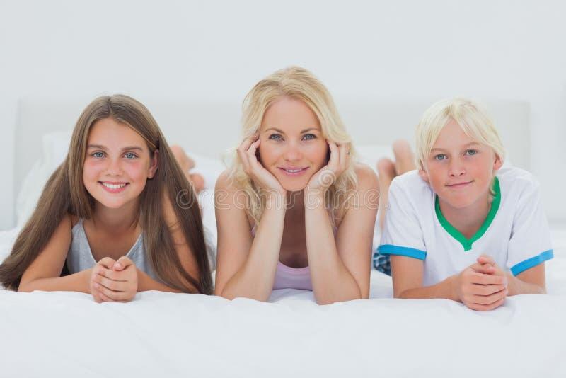 Hermanos y madre que mienten en cama fotografía de archivo libre de regalías