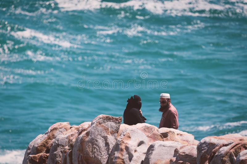 Arabic adult couple standing at the view point in coastal town. HERMANUS, SOUTH AFRICA - NOVEMBER, 2018: Arabic adult couple standing at the view point in royalty free stock photo