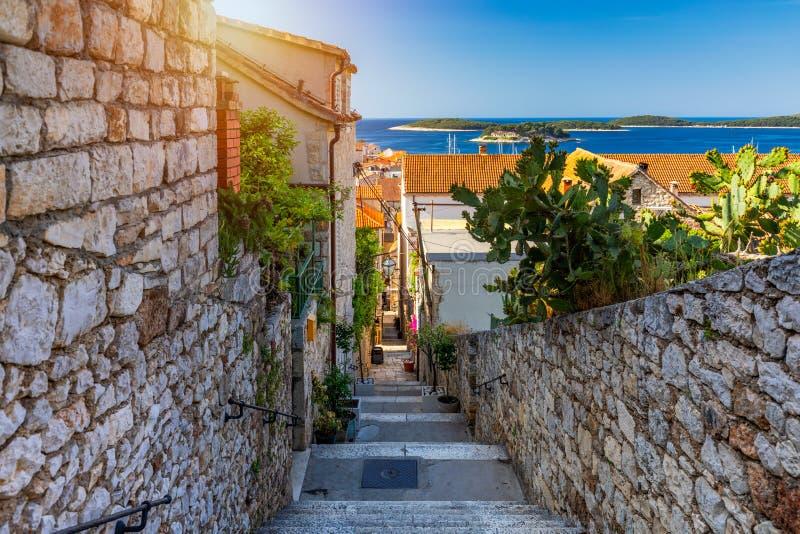 Hermosa calle con flores en la ciudad de Hvar, isla de Hvar, Dalmatia, Croacia Antigua calle mediterránea, ciudad de Hvar Viejo A imagenes de archivo