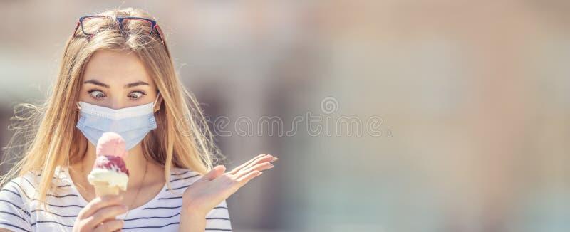 Hermosa chica con una máscara en la cara mirando hacia abajo a un helado en la mano con una mirada cruzada y un gesto de mano des foto de archivo libre de regalías