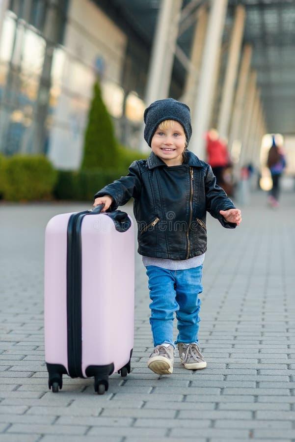 Hermosa chica feliz viaja con una elegante maleta El pequeño viajero va al viaje desde el aeropuerto foto de archivo