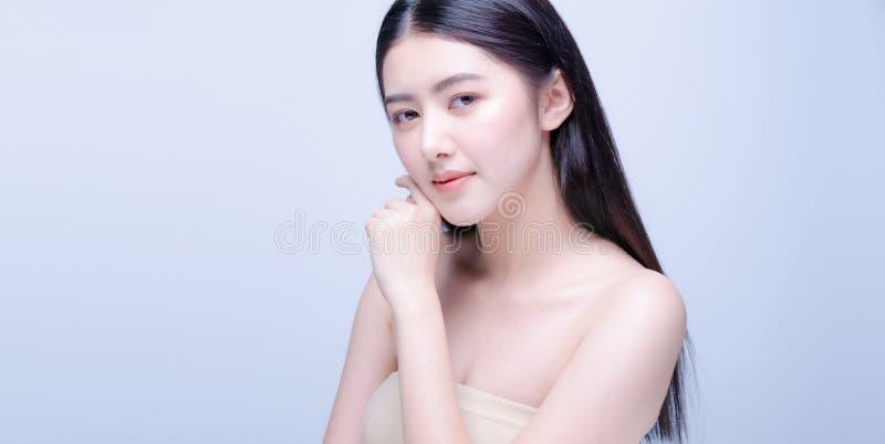 Hermosa joven asiática con la piel limpia y fresca mira la cámara. Cuidado de la cara de belleza femenina. Tratamiento facial. C fotos de archivo libres de regalías