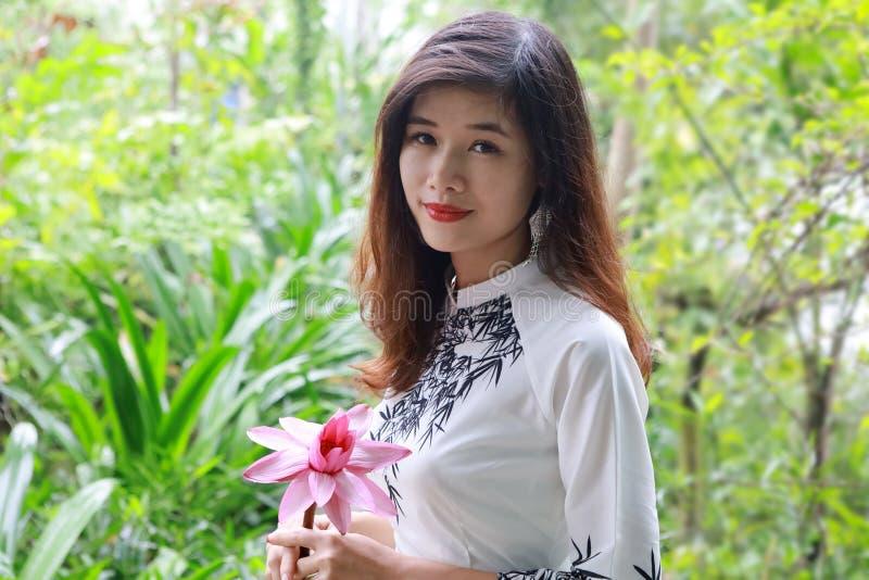 Hermosa joven asiática sosteniendo una gran flor rosa en el jardín botánico fotos de archivo libres de regalías