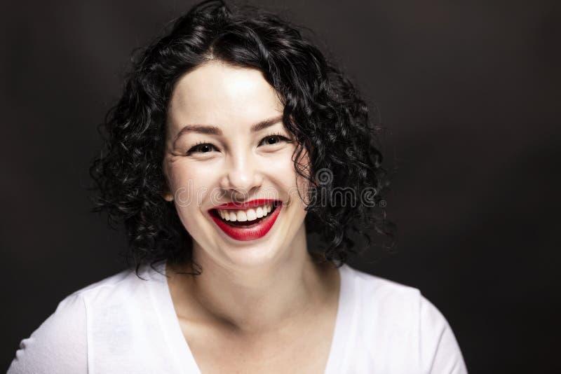 Hermosa joven con una camiseta blanca se está riendo. Brunette brillante con pelo rizado Fondo negro Cierre foto de archivo