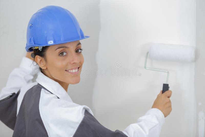Hermosa joven pintando la pared en la habitación fotos de archivo
