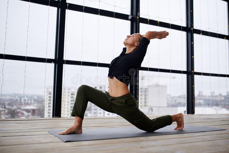 Hermosa joven practica yoga asana Virabhadrasana 1 - guerrera pose 1 en la clase de yoga imagen de archivo libre de regalías