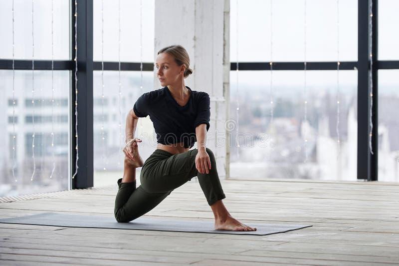 Hermosa joven practica yoga asana Virabhadrasana 1 - guerrera pose 1 en la clase de yoga imagenes de archivo