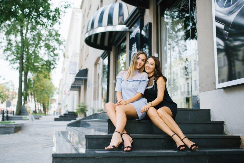 Hermosa madre e hija adulta sentadas en las escaleras del porche abrazándose y sonriendo, son felices. Concepto de relaciones mut fotografía de archivo libre de regalías