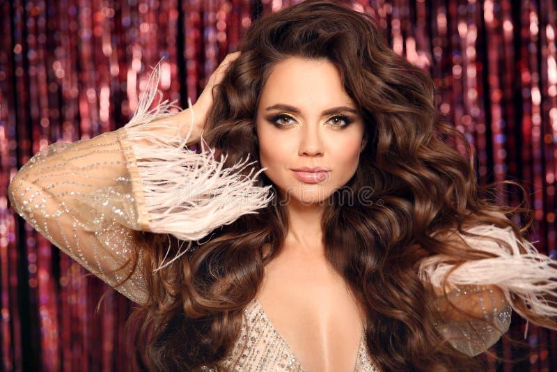 Hermosa morena con cabello ondulado sano La belleza maquillada Chica de moda vestida con glamour Aislada con brillantes luces de  foto de archivo