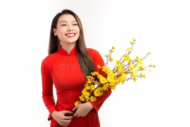 Hermosa mujer asiática vistiendo el tradicional Ao dai vistiendo una flor de melocotón en Tet Holiday imagen de archivo libre de regalías